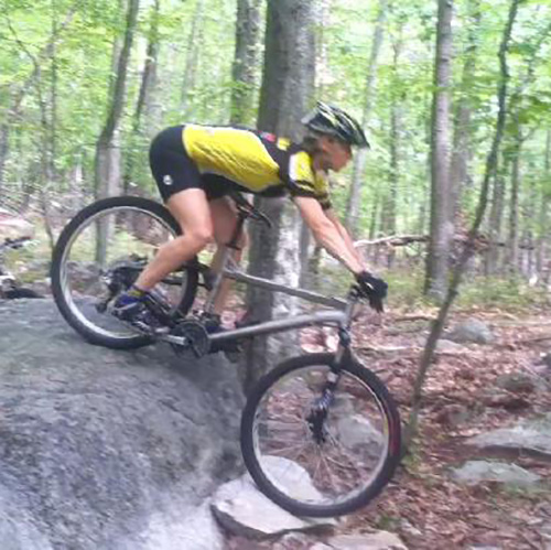 Mountain biker rolling down a larger rock