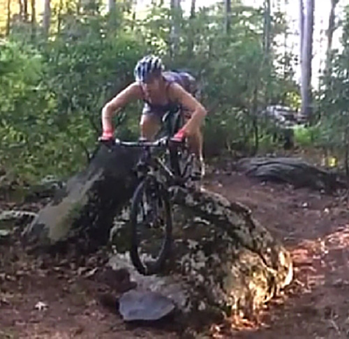 Rock n Roll demonstration of a mountain biker rolling down a larger rock.
