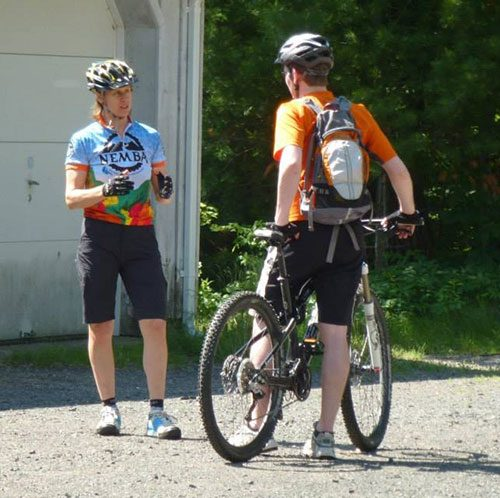 Private mountain bike coaching session with Michael standing over bike and Coach Margie Bowen