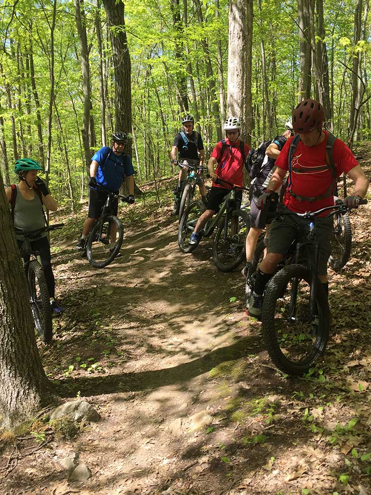 Mountain bikers lined up on side of trail