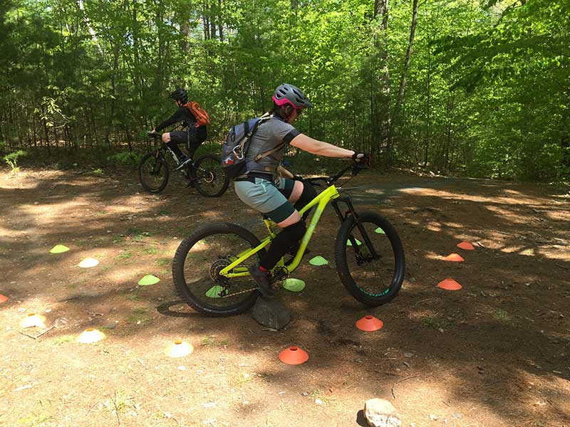 Mountain biker practicing turn with obstacle in trail