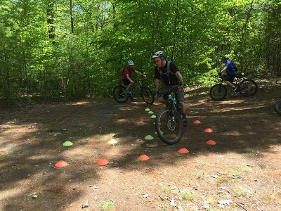 Mountain biking skills clinic with riders practicing tight turns