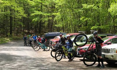 Mountain bikers standing with bikes in front of cars