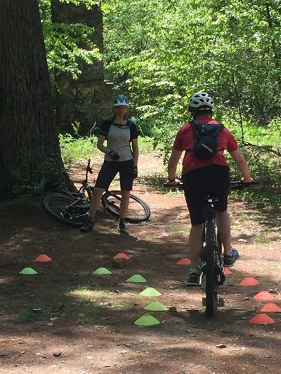 Mountain biker practicing 90-degree turn in a skills clinic