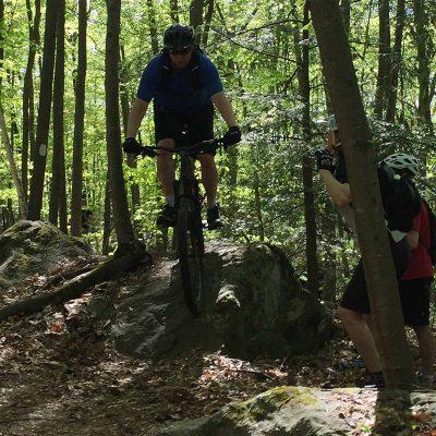 Mountain biker riding down a rock